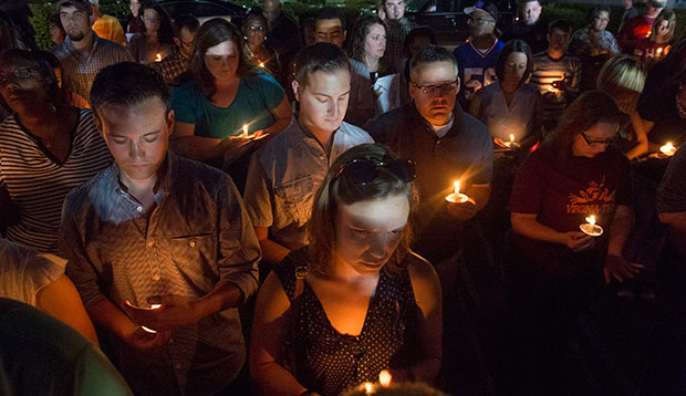 People attend a candlelight vigil in front of the WDBJ-TV station in Roanoke, Virginia, August 27, 2015, a day after reporter Alison Parker and cameraman Adam Ward from the station were killed during a live broadcast.