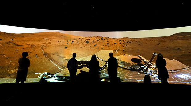 "People look at the ""Mars Window,"" a projection of images taken by NASA's Mars Curiosity rover, at the Visions of the Universe exhibition at the National Maritime Museum in London, June 5, 2013."