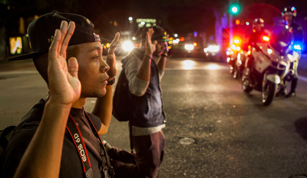 Protesters kneel down with their hands up in front of police officers in Los Angeles, California, on November 26, 2014.