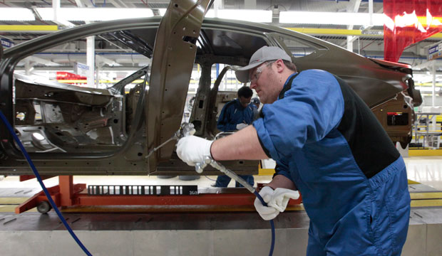 An assembly line employee works on a car in Sterling Heights, Michigan, on March 14, 2014.