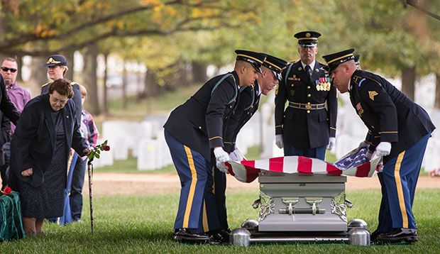Service members lay an American flag on the casket of a soldier on October 26, 2015.