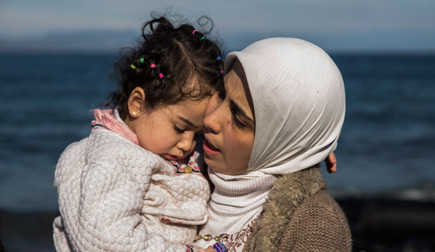 A Syrian mother hugs her child after arriving at the Greek island of Lesbos on an overcrowded inflatable boat on October 27, 2015.