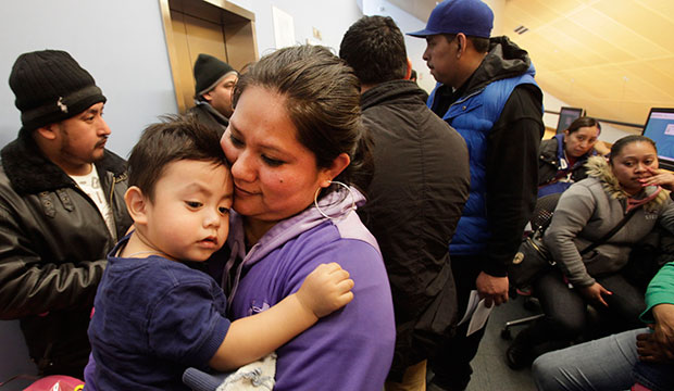 A woman holds her son as she waits in line to apply for a municipal identification card on the first day they were available at the Bronx Library Center in New York, January 12, 2015.