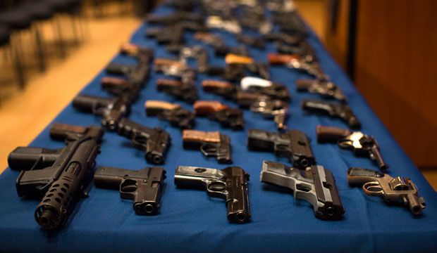Nearly 100 confiscated illegal firearms—many from out-of-state sources, notably South Carolina—rest on a table before a press conference on October 12, 2012, in New York City.