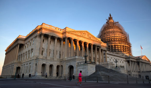 A jogger runs past the the U.S. Capitol at sunrise on October 22, 2015.