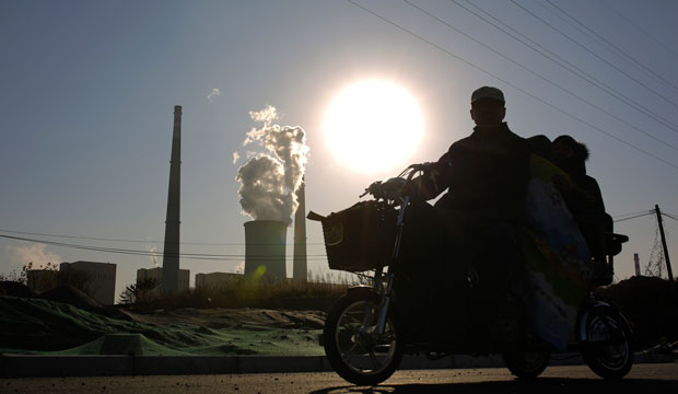 A family riding an electric tricycle bike is silhouetted against the sun setting on a coal-fired power plant in Beijing, China, November 2014.