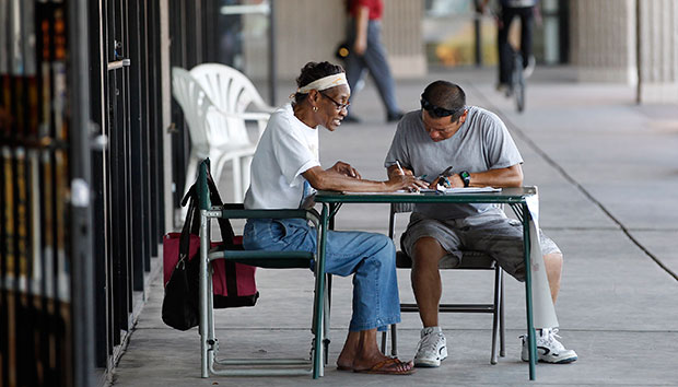 A volunteer for President Barack Obama's re-election campaign, left, registers someone to vote as volunteers register new voters at a table set up in front of campaign headquarters at a local shopping plaza in Phoenix, June 2012.