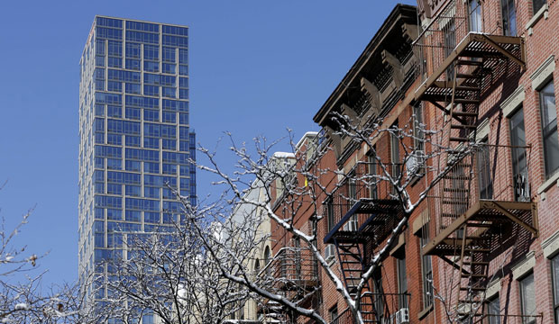 A luxury rental building rises high above other residential buildings in the East Harlem section of New York City, February 3, 2015.