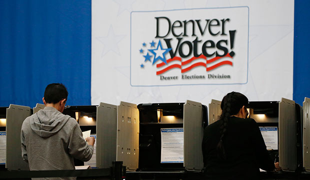 A pair of voters cast ballots during the statewide general election, November 3, 2015, in Denver.