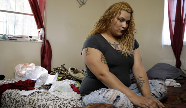 A transgender woman, once homeless, poses for a photo in her apartment.