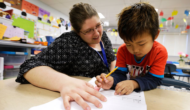 Elementary school teacher works with a kindergarten student in Columbus Junction, Iowa.