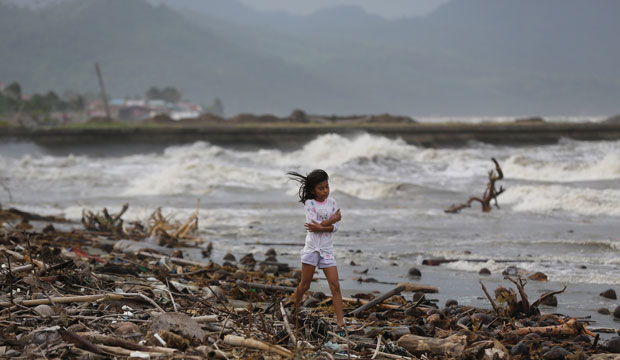 A girl walks along the shore as strong waves from Typhoon Hagupit hit Atimonan in the eastern Philippines on December 6, 2014.