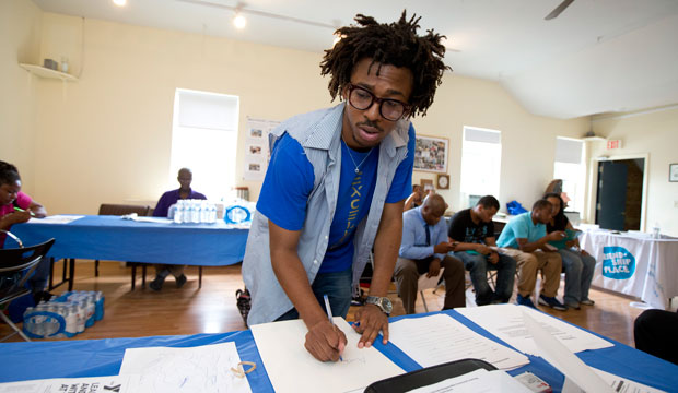AmeriCorps volunteer John Harris III helps coordinate a jobs fair program for job seekers in Washington on July 31, 2013.