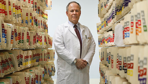 A doctor poses for a picture among patient files at a New York hospital, June 2009.