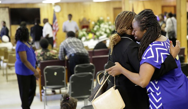 A reverend embraces a church member who is grieving.