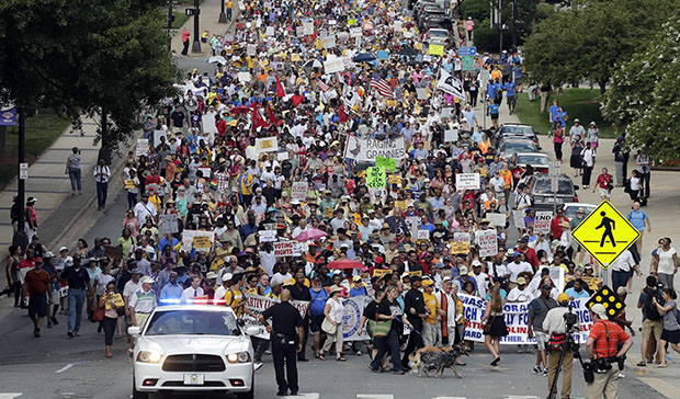 Demonstrators march through the streets of Winston-Salem, North Carolina, July 13, 2015, after the beginning of a federal voting rights trial challenging a 2013 state law.