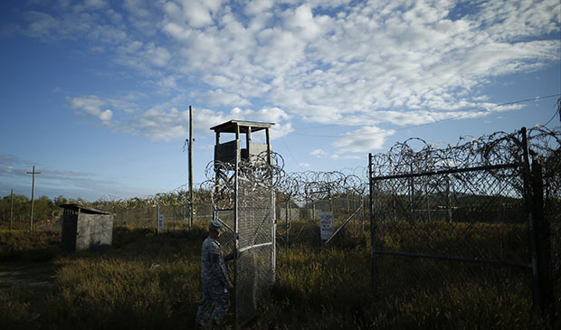 In this photo reviewed by the U.S. military, a soldier closes the gate at the now abandoned Camp X-Ray, which was used as the first detention facility for Al Qaeda and Taliban militants captured after the September 11 attacks at Guantanamo Bay Naval Base, Cuba, November 2013.