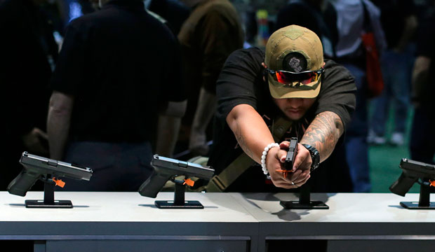 A buyer checks out various hand guns on display during the Shooting, Hunting, and Outdoor Trade Show on January 14, 2014, in Las Vegas.