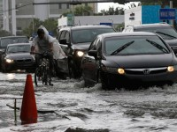 A cyclist and vehicles negotiate heavily flooded streets