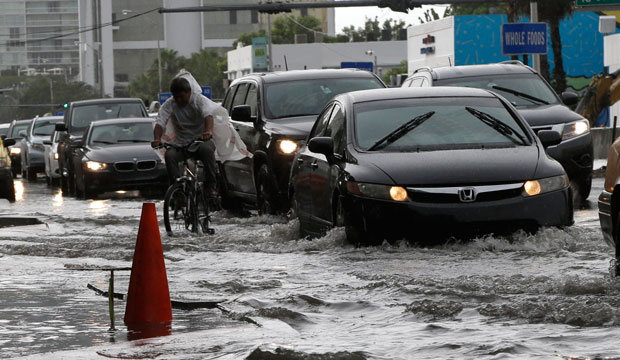 A cyclist and vehicles negotiate heavily flooded streets as rain falls, September 23, 2014, in Miami Beach, Florida.