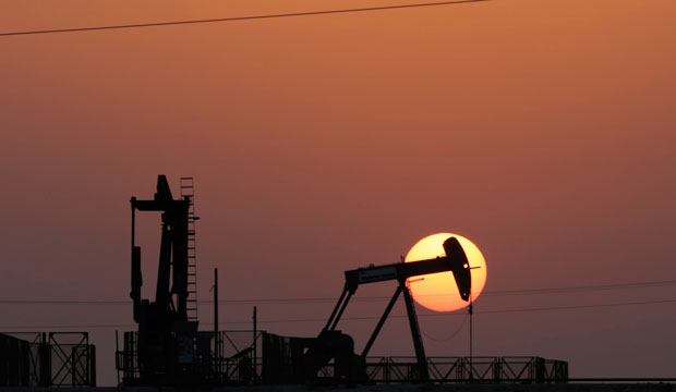 An oil pump works at sunset on September 30, 2015, in the desert oil fields of Sakhir, Bahrain.
