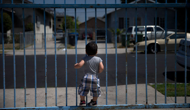 One-year-old Joshua Tinoco, who has been declared an immigration enforcement priority for the United States, clings to a gate at his relative's home in Los Angeles.