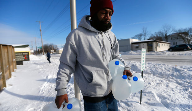 In this February 3, 2015, photo, Lemott Thomas carries free water being distributed at the Lincoln Park United Methodist Church in Flint, Michigan.