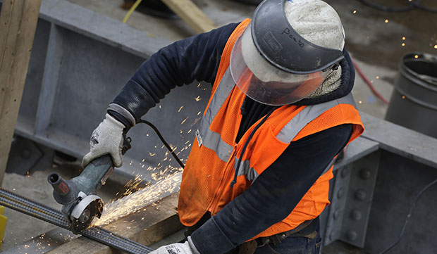 Sparks fly as a construction worker uses a grinder to cut through steel reinforcing bars, February 1, 2016, in New York.