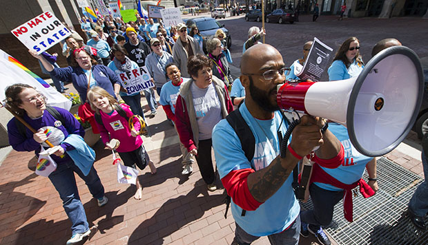 Dominic Dorsey uses a megaphone as he leads a group of opponents to Indiana S.B. 101, the state's Religious Freedom Restoration Act, in a march toward Lucas Oil Stadium in Indianapolis, April 4, 2015.