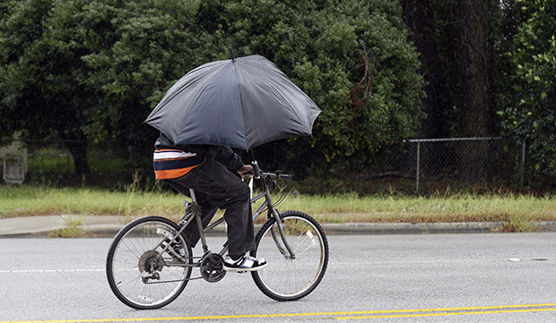 A bicyclist shields himself against the rain in Marion, South Carolina, October 4, 2015.