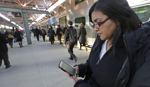 A woman checks a news website on her smartphone before boarding a train home at the end of her workweek in Chicago, March 2015.