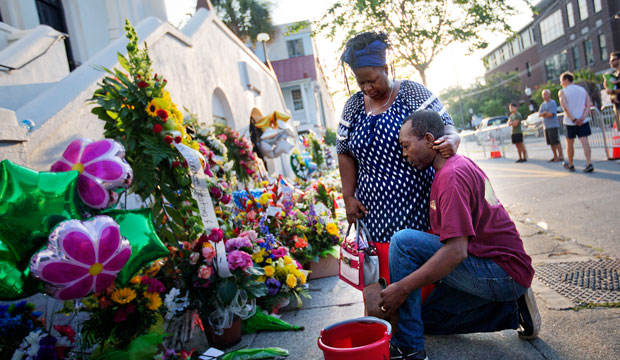Allen Sanders kneels next to his wife Georgette as they pray at a sidewalk memorial in memory of the Mother Emanuel shooting victims on June 20, 2015, in Charleston, South Carolina.