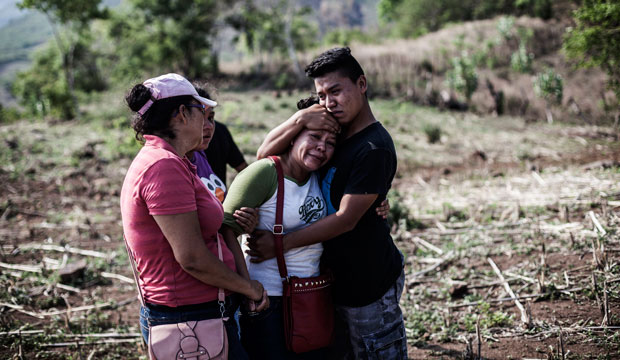The son of Alberto Hernandez—a man who was kidnapped and murdered by gang members—embraces his mother in a rural area near Caserío el Chumpe, El Salvador, June 2015.