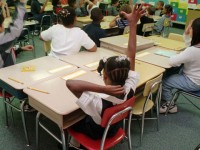 Third-grade students raise their hands