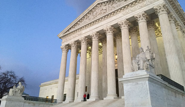 People stand on the steps of the U.S. Supreme Court on February 13, 2016, in Washington, D.C.