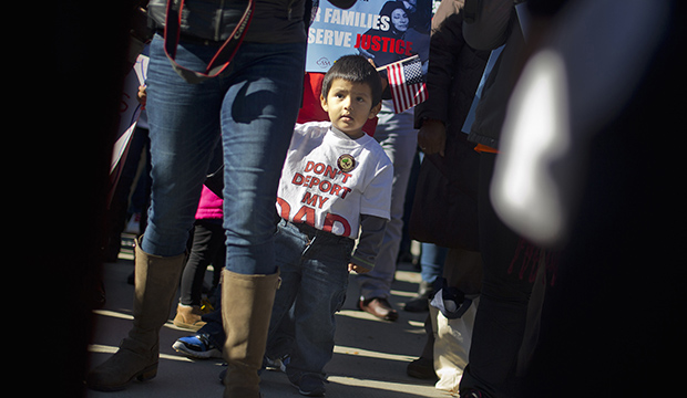 A 2-year-old watches his parents take part in a rally for immigration reform at the Supreme Court in Washington, November 20, 2015, on the one-year anniversary of President Barack Obama's announcement concerning DAPA.