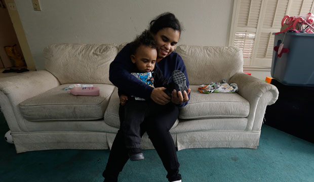 A woman gets her son dressed before leaving home for her job in Sacramento, California, on May 15, 2015.