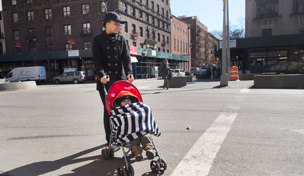 Beonca Williams crosses the street with her 1-year-old son Joshua Felix outside the Regent Family Residence, left, March 12, 2015, in New York.
