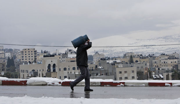 A Palestinian man carries a gas tank in the West Bank town of Nablus in December 2013.