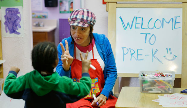 A pre-kindergarten teacher talks with a student on October 21, 2014, in Seattle, Washington.