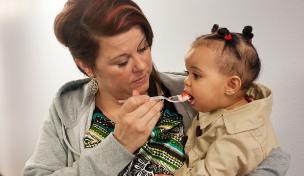 A mother feeds her daughter at the Net Health Women, Infants, and Children Department in Tyler, Texas, in March 2015.