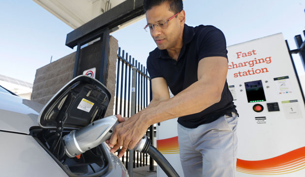Darshan Brahmbhatt plugs a charger into his electric vehicle at the Sacramento Municipal Utility District charging station in Sacramento, California, on September 17, 2015.