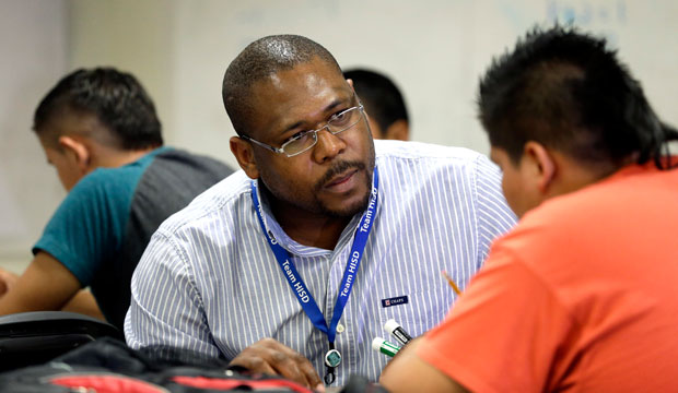 A teacher works with his student at Liberty High School in Houston, Texas, on July 1, 2014.