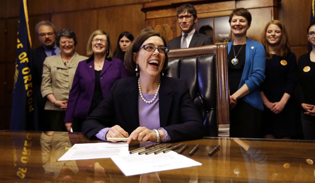 Oregon Gov. Kate Brown (D) smiles after signing an automatic voter registration bill in Salem, Oregon, on March 16, 2015.