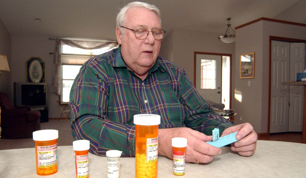 A man looks at his prescription medications at his home in Litchfield, Minnesota, in 2006.