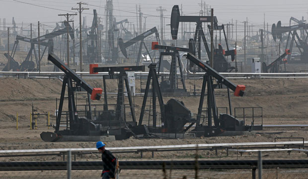 A person walks past pump jacks operating at the Kern River Oil Field in Bakersfield, California, on January 16, 2015.