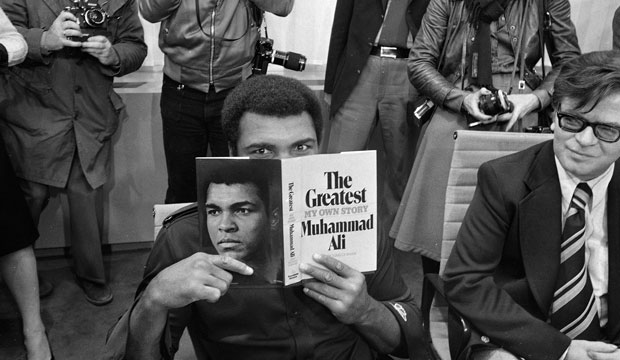 "Muhammad Ali peers over a copy of his autobiography, ""The Greatest: My Own Story,"" in Frankfurt, Germany, on October 10, 1975."