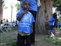 Peter Yabadi, 2, stands next to his mother
