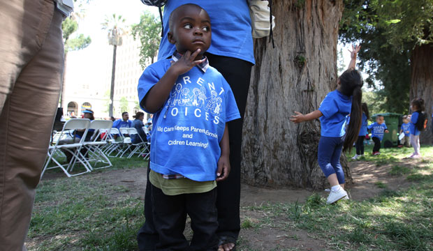 Peter Yabadi, age 2, stands next to his mother, Bernadette Yabadi, at a rally calling for increased child care subsidies at the Capitol in Sacramento, California, on May 6, 2015.