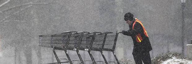 A worker pushes shopping carts back to a grocery store as snow falls.